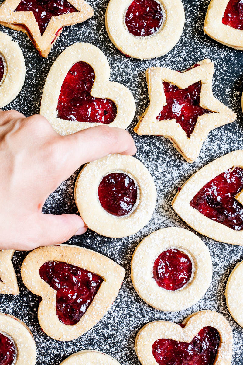 Light brown cookies in shapes of heart, star and circle filled with red jam is scattered around dusted with powdered sugar on a black surface. A hand is taking one cookie from the middle.