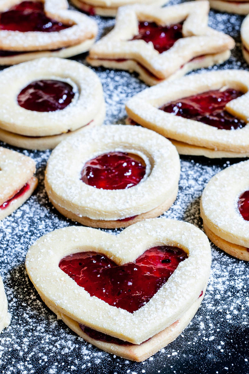 Light brown cookies in shapes of heart, star and circle filled with red jam is scattered around and dusted with powdered sugar on a black surface.