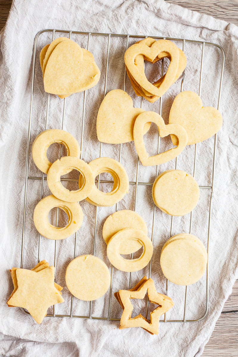 Light brown cookies in shapes of heart, star and circle are scattered on a wire rack.