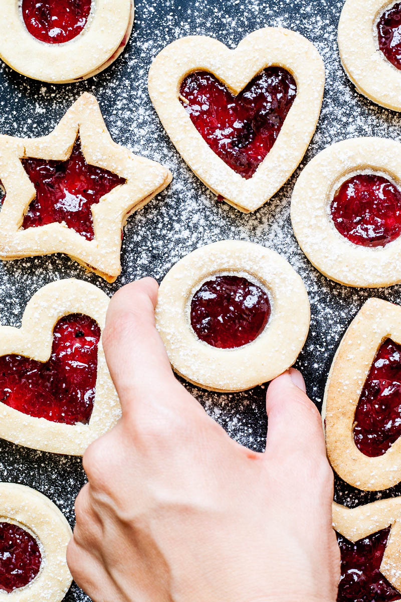 Light brown cookies in shapes of heart, star and circle filled with red jam is scattered around dusted with powdered sugar on a black surface. A hand is taking a cookie from the middle.