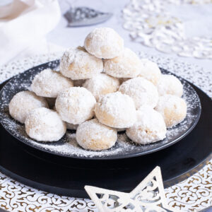 A stack of ball-shaped cookies on a black plate. It is dusted generously with powdered sugar so they are white as snow balls. White and silver christmas ornaments are placed next to them.
