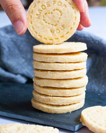 A stack of thin round cookies on a black board. A hand is holding the top cookie