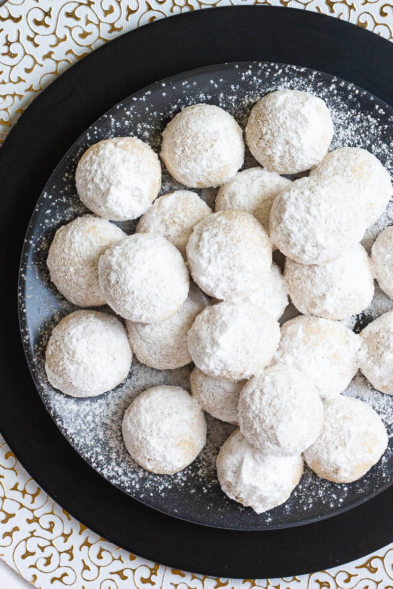 A stack of ball-shaped cookies on a black plate from above. It is dusted generously with powdered sugar so they are white as snow balls.