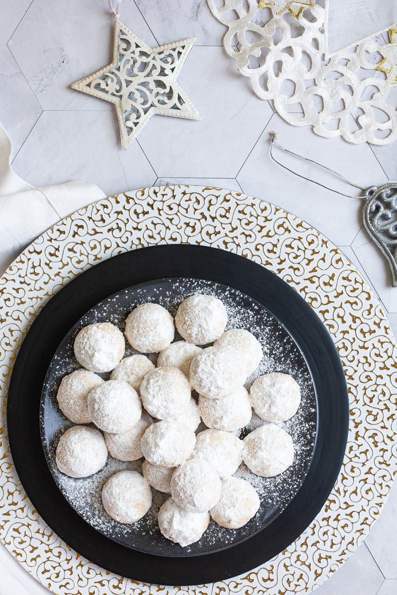 A stack of ball-shaped cookies on a black plate from above. It is dusted generously with powdered sugar so they are white as snow balls. White and silver christmas ornaments are placed next to them.