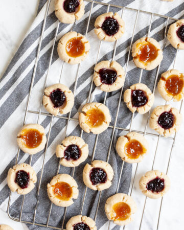 Several round cookies with orange and purple jam filling placed on a wire rack from above.