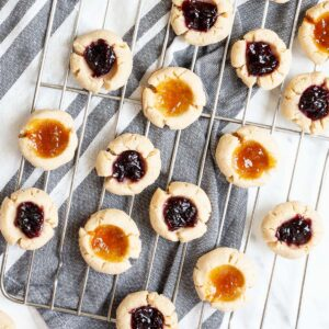 Several round cookies with orange and purple jam filling placed on a wire rack.